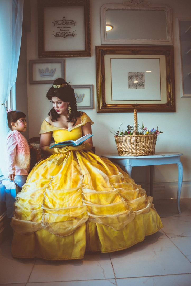 A beautiful Princess Belle character, dressed in her impressive ballgown, discusses a storybook with a wide-eyed little girl at the grand opening of The French Confection Co.